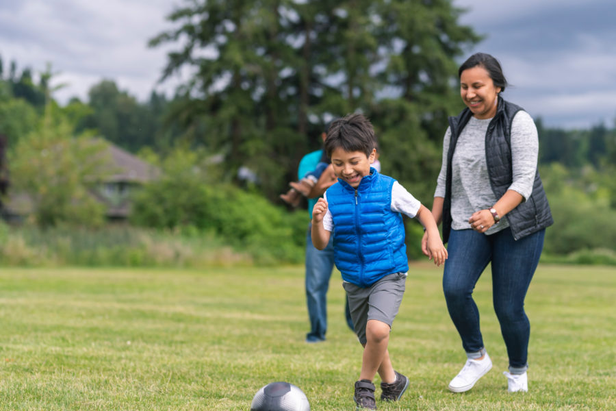 Mom and dad run around a field with their two young children and play a combination of soccer and tag. Dad is holding the youngest, and the older, a boy, is trying to get away from mom. They all have big smiles.